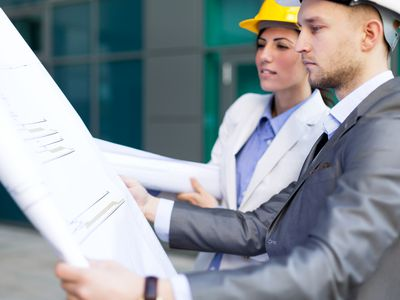 Workers on a construction site reviewing a gantt chart.