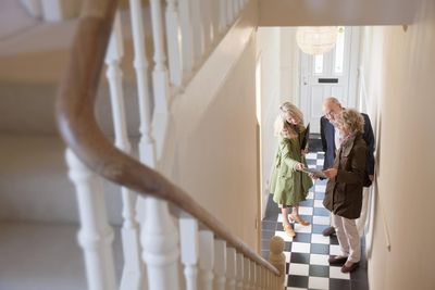 A real estate agent shows a home to a senior couple