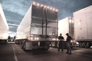 Two men standing at a trucking station