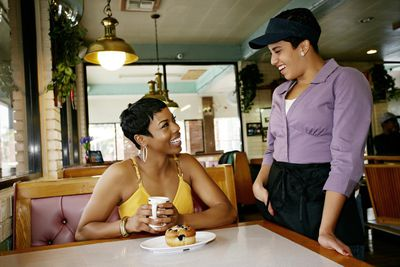 Waitress smiling at a table and offering great customer service to a customer.