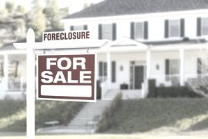 Foreclosure/For Sale Sign in front of large white house