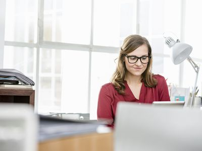 A picture of a woman at a desk working on computer