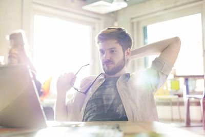 Man working on computer in sunny office