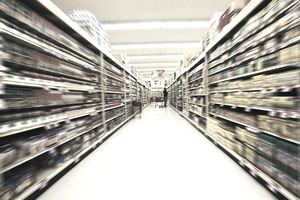 Long view of a shopper in a big-box supermarket aisle