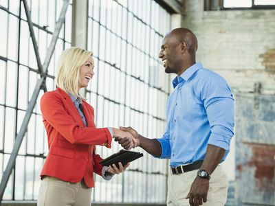 Business people shaking hands in warehouse
