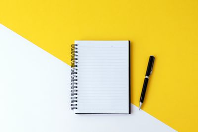 spiral notebook against yellow and white background