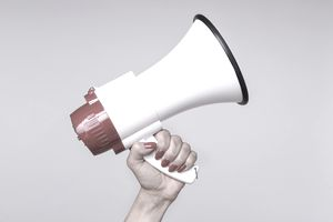 Cropped Hand Of Woman Holding Megaphone Against White Background