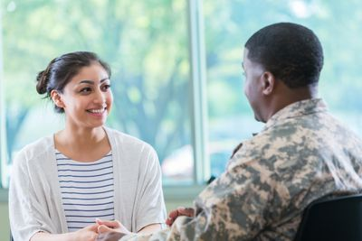 A woman in business dress is talking to a man in a military uniform.