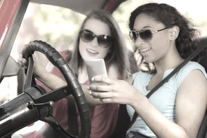 Teenage girls texting while driving a car