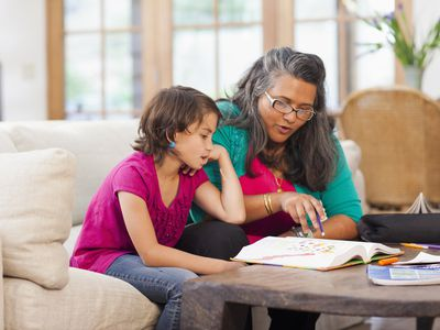 Mother and daughter looking at an open textbook on a coffee table