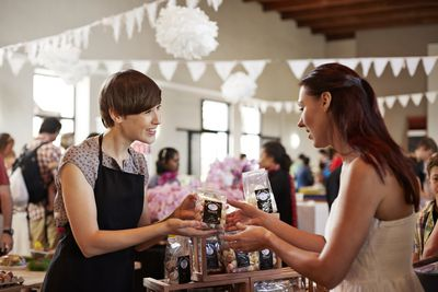 Saleswoman handing a product to a customer, representing brand identity.