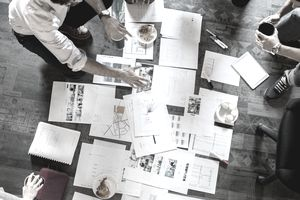 In this overhead photograph, a group of small business staffers review charts and documents on the floor of an open plan office space.
