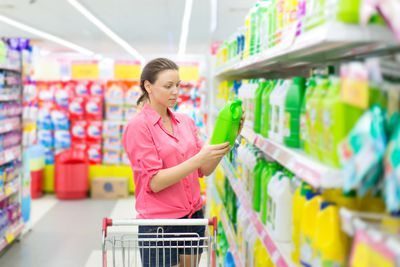 A woman examining a cleaning product at a grocery store