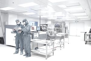 Two workers talking in a clean room.