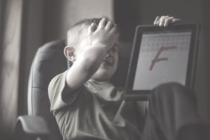 Boy with his hand on his forehead showing failing grade on a tablet