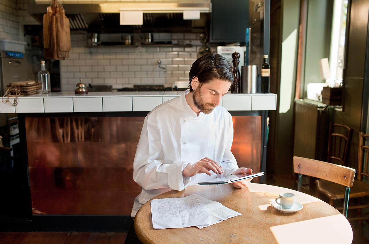 Small restaurant owner dressed in chef whites using a tablet to enter expenses into an accounting software system.