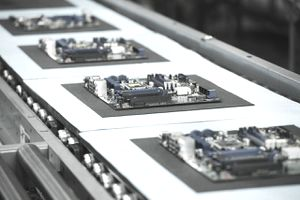 Several motherboards move on a conveyor in manufacturing facility.