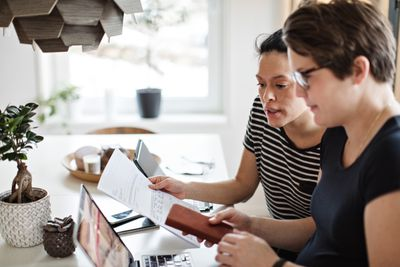 Lesbian couple discussing over financial bills while using laptop at table