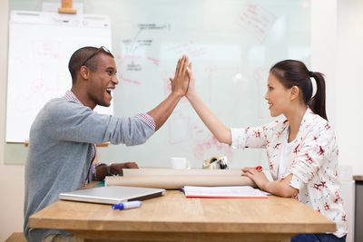 Motivated employees congratulating each other