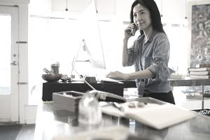 Female shop owner talking on telephone at computer behind counter