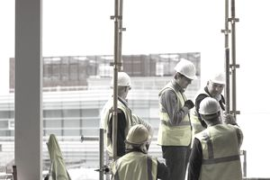 Workers on construction site discuss plans for construction site