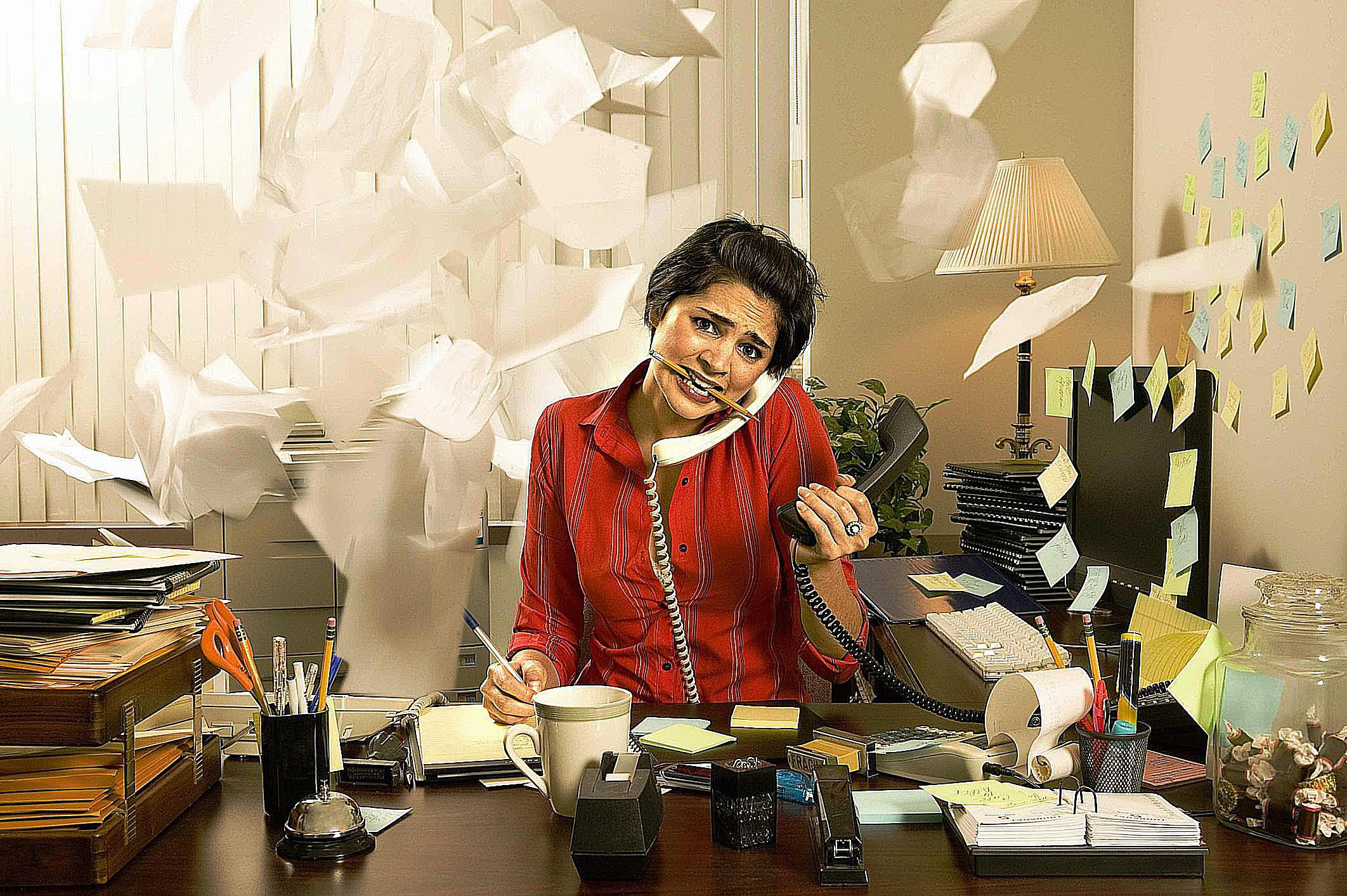 Woman trying to multitask surrounded by a mess of flying papers
