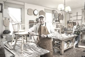 An elderly wood worker takes a break from the chair he's building to regard the camera that's appeared in his brightly lit shop, while another, younger, wood worker in the background leans against a bench.