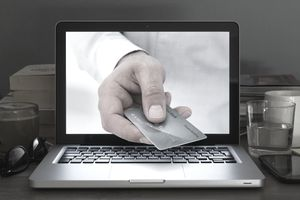 Hand reaching out of computer with a credit card