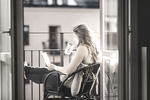 Side view of woman drinking water while reading guidebook at balcony