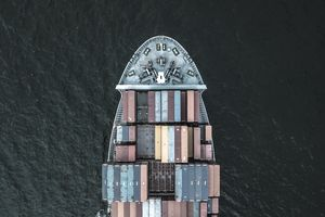 Overhead view of an international container cargo ship filled with parallel importing market goods.