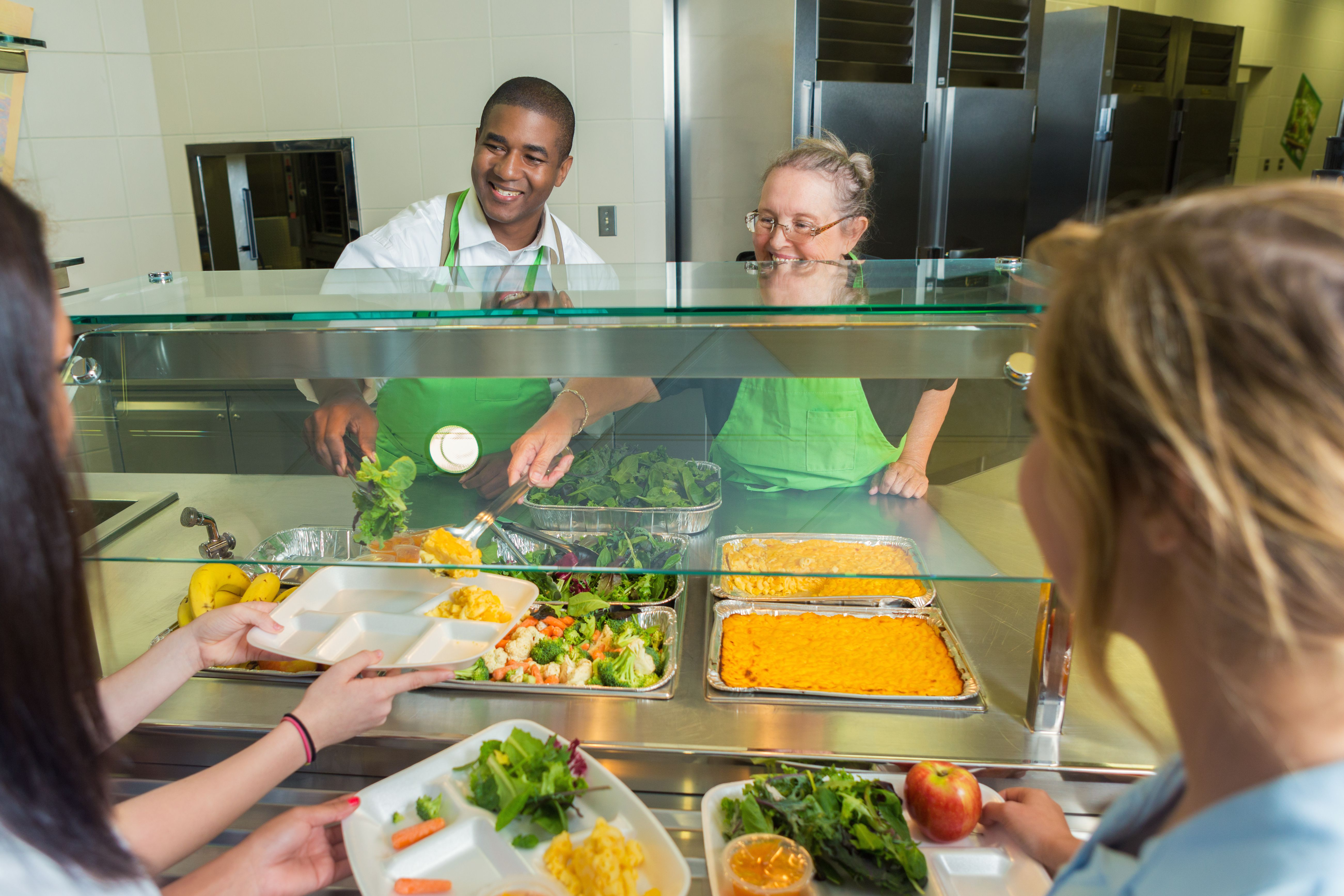 Diverse cafeteria works serve high school students