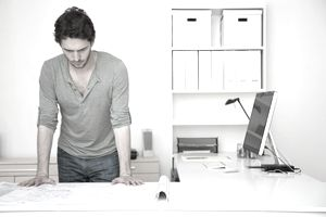 Caucasian man looking at blueprints in office