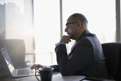 A lawyer sitting in an office using a laptop preparing an email.