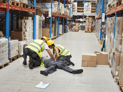 Warehouse workers giving a coworker first aid for an on-the-job injury that will likely get him worker's compensation.