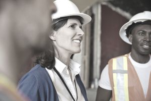 Smiling female architect standing with team at construction site