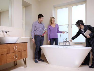 Part-time real estate agent showing a bathroom to a couple.