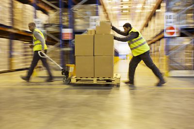 Workers moving product in a warehouse or distribution center