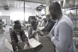 Father and daughters volunteering, filling boxes for food drive in warehouse