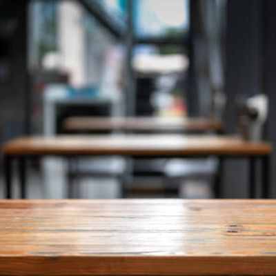 Row of restaurant tables in an empty restaturant space