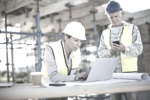 builders on a job site working on digital devices