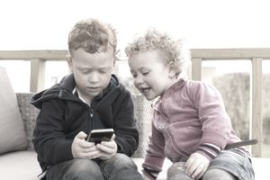 Little red-haired boy and girl looking at smartphone