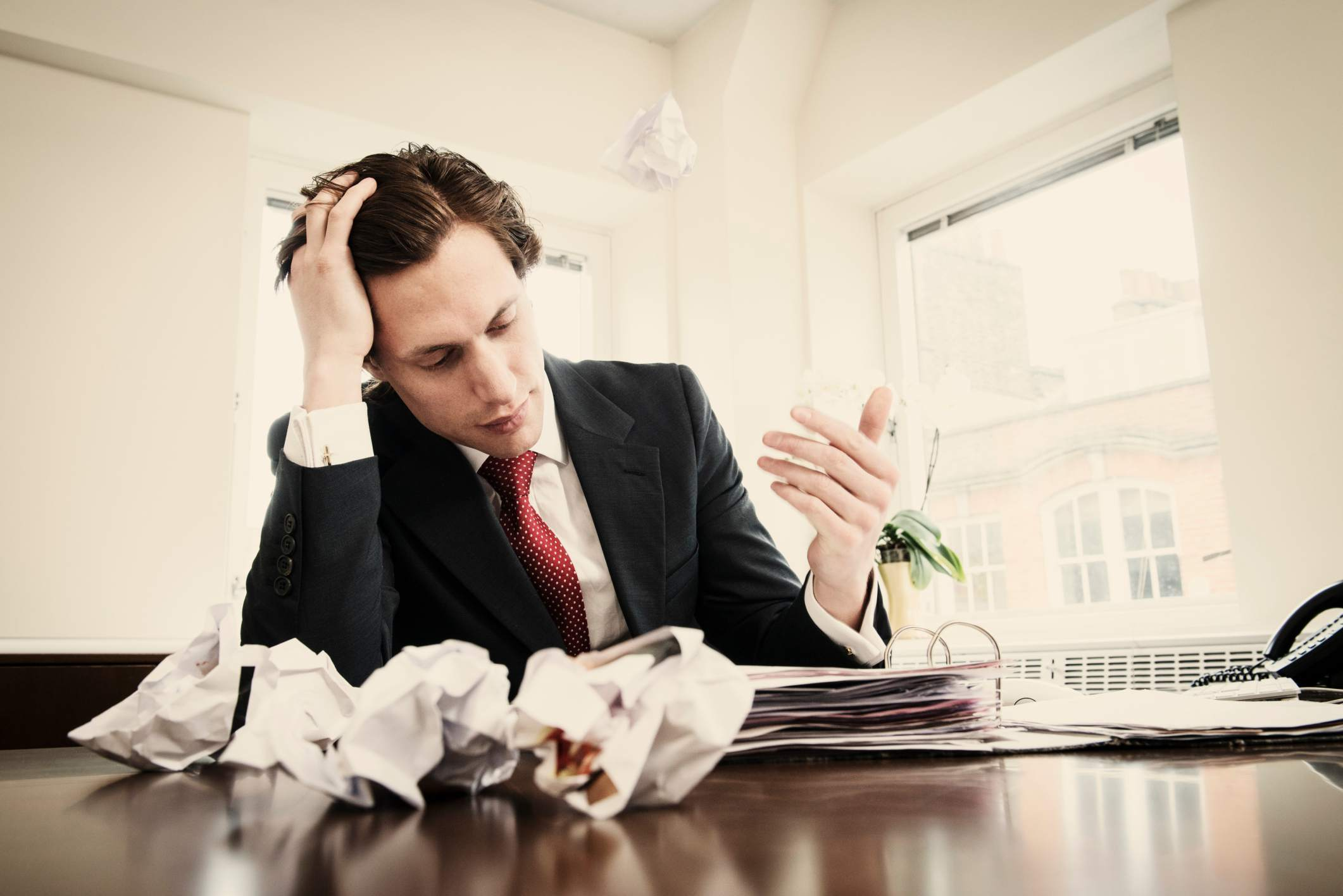 An office worker surrounded by a binder and crumpled paper