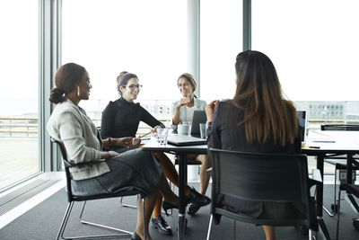four women in a meeting talking about work