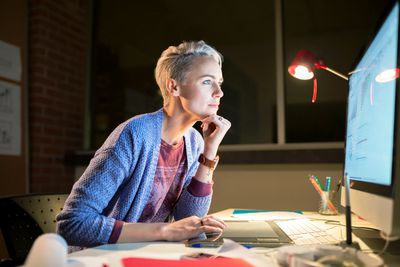 Woman working late at computer in office