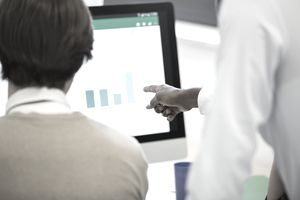 Two business people looking at graphs on a computer screen, representing the concept of market share.