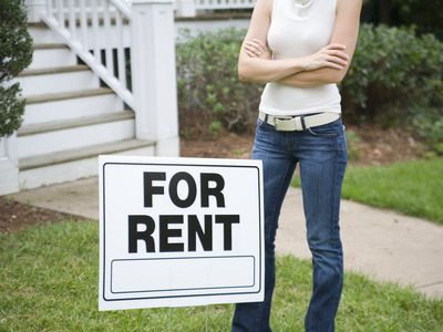 Woman in jeans standing next to a for rent sign on a lawn