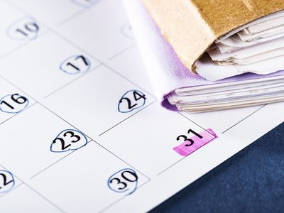 Close-up of file folders and calendar with dates circled and highlighted