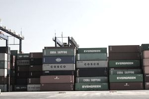 Export containers wait on a dock for loading onto a ship.