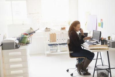 Mixed race businesswoman working at desk