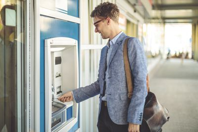 A man inserts his credit card into an ATM terminal.